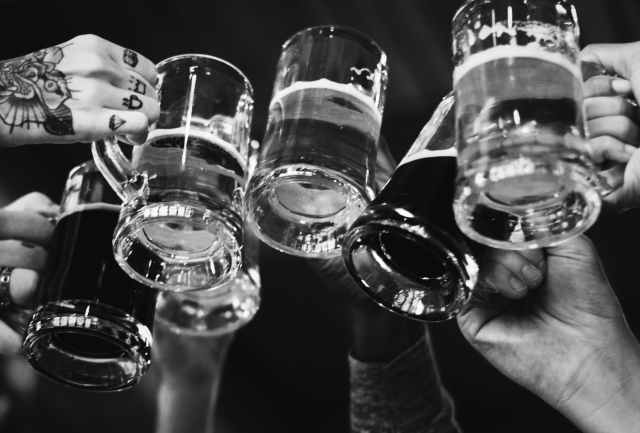 grayscale photo of people cheers glasses